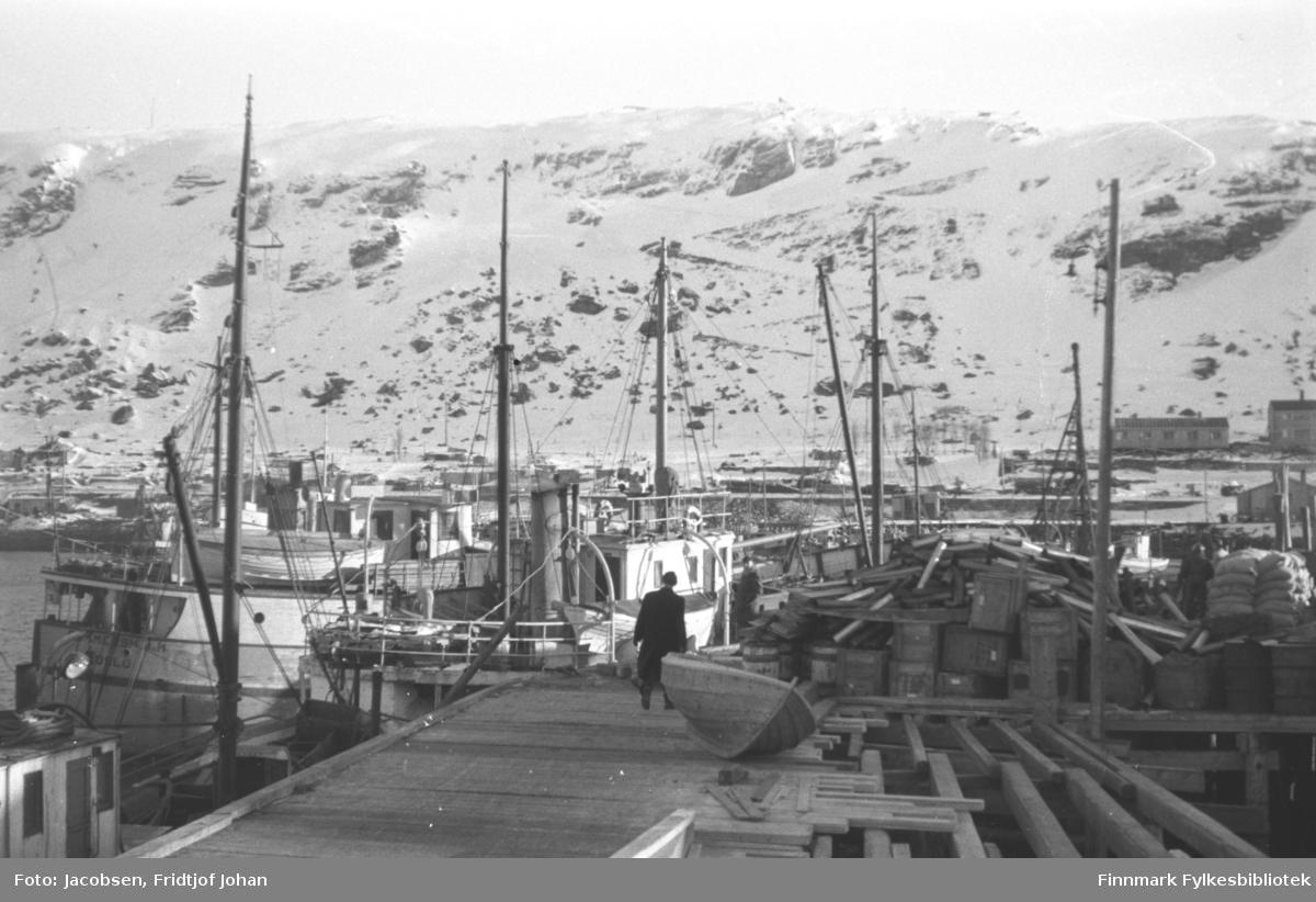 Vinter i Hammerfest havn. Store mengder bygningsmateriell, kasser og sandsekker ligger i stabler til høyre på kaia. Mannen midt på bildet er Ragnvald Jacobsen, iført mørke klær. Rett bak han ligger en liten trebåt. Flere båter ligger fortøyd ved kaia og noen brakker ses i bakgrunnen ved foten av fjellet Salen og i strandkanten. Fjellet er stort sett snødekt og sikk-sakkveien ses midt på bildet.