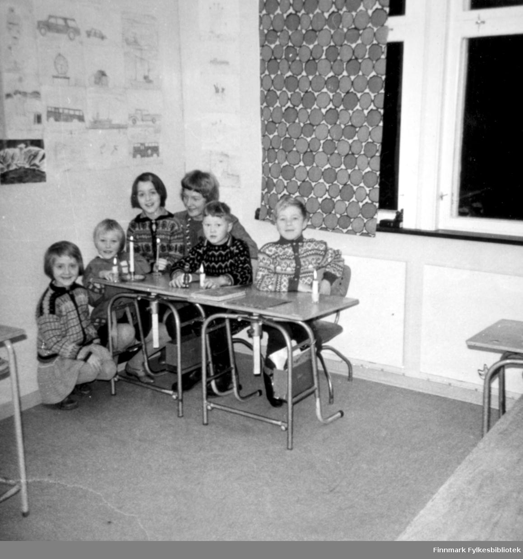 Barna sitter med sin lærer, Britt Ellinor Skjærvøy, i det nye klasserommet som ble bygd på Krampenes skole. I følge vår informant er året trolig 1963. Fra venstre til høyre: Tone Stock (1.klasse), Elinnor Stock (3. klasse), Svanhild Rushfeldt (3. klasse), Britt Ellinor Skærvøy(lærer), Jon August Pleym (3. klasse), Ronny Ananiassen (3.klasse). De sitter ved et par pulter, med levende lys på bordet. På veggen kan man se tegninger trolig laget av barna. Foran vinduet ser man en gardin med sirkel-mønster og på utsiden ser det mørkt ut.Tone, Svanhild, Jon August og Ronny har på seg strikkede kjorter med møster på. Tone og Ellinor har på seg skjørt.