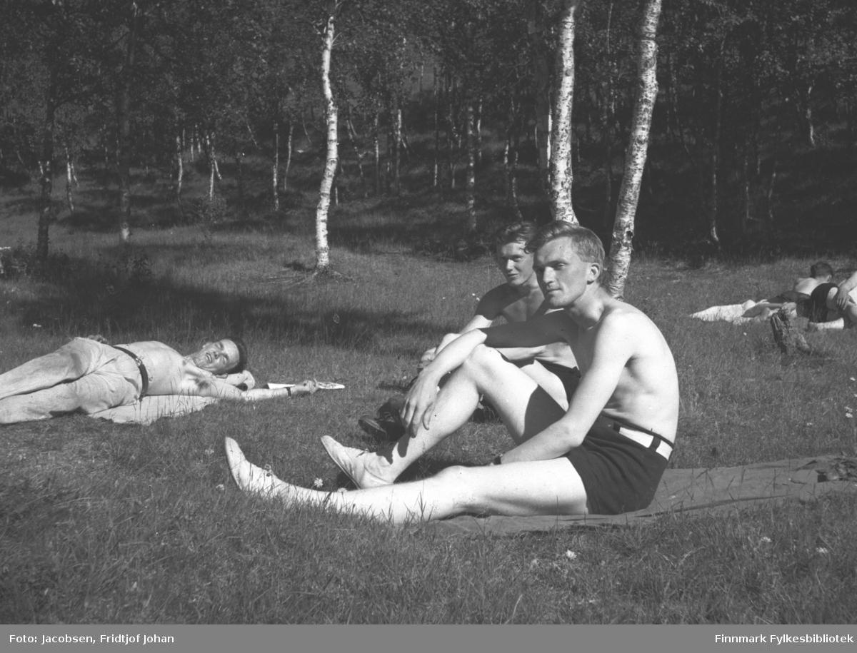 Fridtjof Jacobsen og to venner soler seg i gresset. Alle tre har bare overkropper og de to som sitter har shorts mens mannen som ligger har bukse. De sitter på pledd eller tepper og den flate bakken rundt dem er gressdekt. En skog av løvtrær står på området bak dem. Iflg. informanten er bildet tatt i Tromsø men det kan også være i Alta under Jacobsens militærtjeneste eller en øvelse han deltok i.