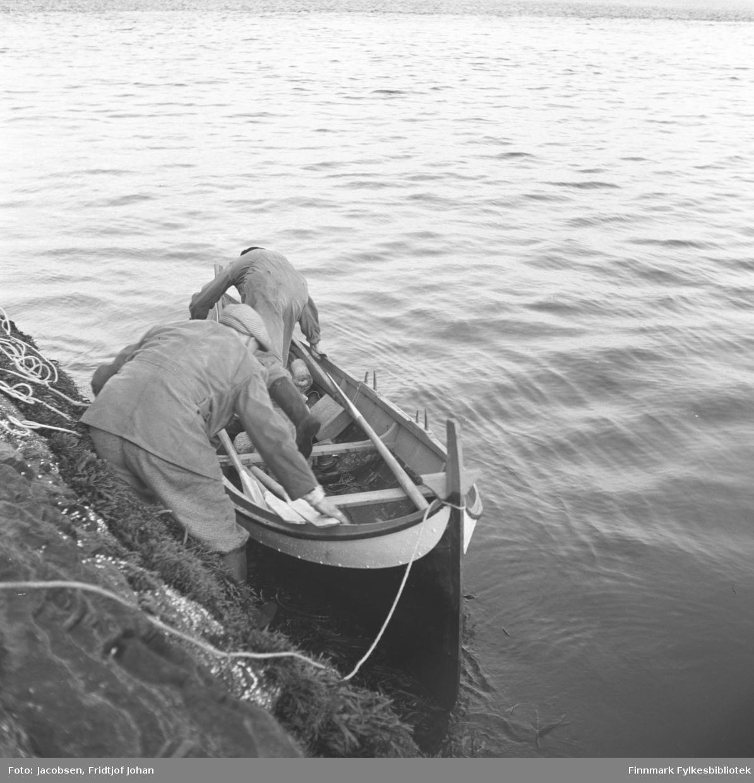 Fridtjof Jacobsen til venstre og hans svigerfar Arne Nakken står foran i båten. Begge to har ganske lyse kjeledresser på seg og Fridtjof har også skyggelue på hodet. Årer ligger i båten og noe tau ligger oppover berget. Dette er sannsynligvis Arne Nakkens Nordlandsbåt og den er avbildet flere ganger i samlingen.