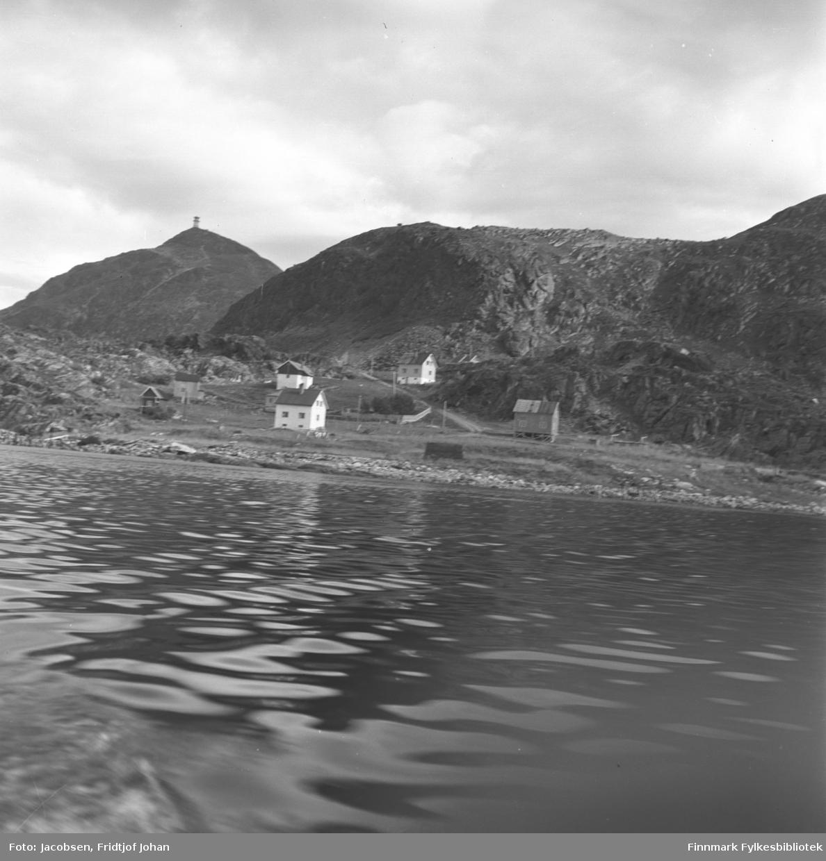 Bildet er tatt fra en båt mot Leirvika som ligger rett vest for Rypefjord. Fem boliger og et naust står på området. Veien fra Leivikhøgda/Rv 94 ses midt på bildet. Fjellet Tyven med masta under bygging ligger til venstre på bildet. Sjøen er blikkstille og det er overskyet.