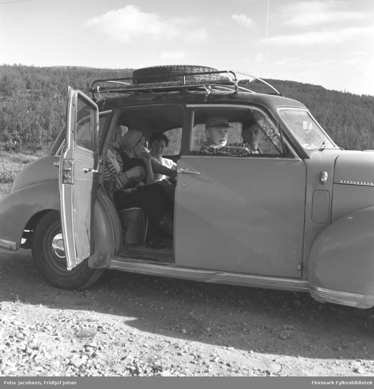 Familien Jacobsen/Nakken på biltur til Sennalandet. Bilen (Bilen er en Studebaker 1946 kfr. logo i bakkant av panseret) tilhører Øystein Nakken som sitter i førersetet. Ved siden av ham sitter Arne Jacobsen i rutet skjorte og skyggelue på hodet. I midten bak sitter hans mor, Aase Randi Jacobsen. Ved siden av henne sitter en ukjent dame iført en hvit overdel. Mannen nærmest kamera i baksetet har en strikkekofte på seg og kan være Arne Nakken. Et reserverhjul ligger oppå lastegrinda på taket og en ås dekket av skog ses i bakgrunnen. Siden det er små fjell/åser som er dekket av skog, er nok bildet tatt i Repparfjord-området.