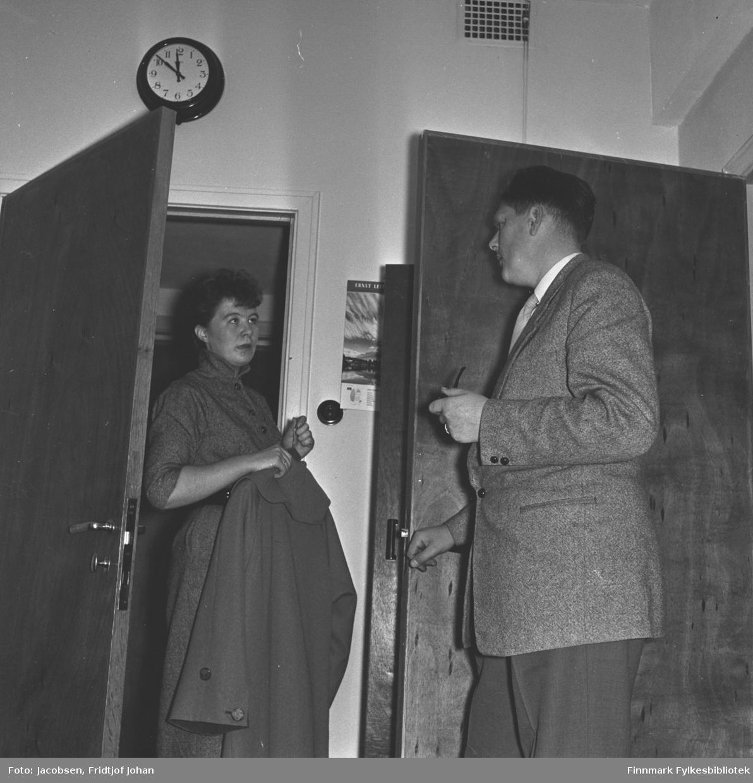 Else Marie Aas Sebergsen til venstre og Tor Todal til høyre står i hver sin døråpning og prater. Tor har en mørk bukse og en noe lysere dressjakke på seg. Han holder en tobakkspipe i sin venstre hånd. Else har en mørk kjole på seg og holder en kåpe i hendene. Begge dørene er mørke og et veggur henger på veggen over Else.