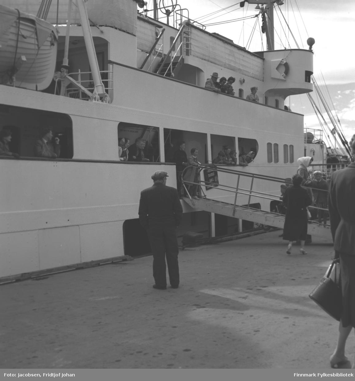 Hurtigruta klar for avgang fra Hammerfest. Til venstre for landgangen står Aase Randi (med skaut), Arne og Pauline Jacobsen