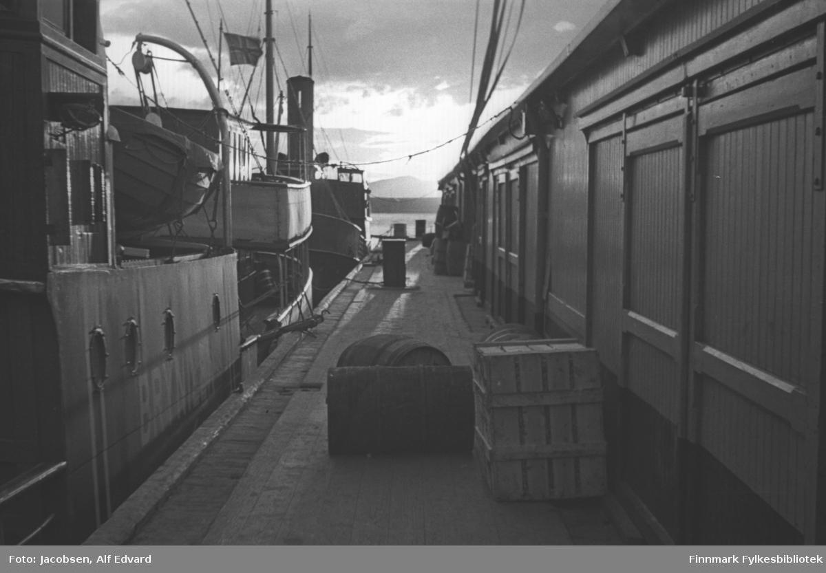 Dampskipskaia i Hammerfest. Til venstre på bildet ligger to av FFRs lokalbåter. Den nærmeste er Brynilen. Det er bare deler av rorhuset og salongen som vises på bildet. En livbåt henger i et stativ mellom rorhuset og salongen. Det norske flagget henger fra en tynn flaggstang på hekken. Bak Brynilen ligger den andre FFR-båten. Det kan se ut som det er en ferge pga rorhusformen. Flere tønner ligger og står på kaia og en kasse står inntil veggen. Bygget til høyre er forholdsvis lyst, har stående panel og flere store porter ses langs veggen. Sola bryter gjennom skylaget og en liten del av Fuglenesodden kan ses mellom båtene og bygget.