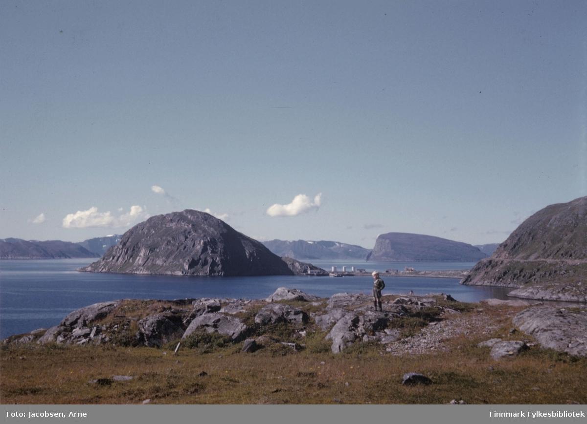 Arne Jacobsen på tur i fjellet ovenfor Rypefjord en solfylt sommerdag. Noe berg/stein der han står og gress i forgrunnen. Fjellet til venstre på bildet er Rypklubben og til høyre er Rypefjell med Rypklubbveien. Mellom dem står tankanlegget til Esso på Rypklubbeidet. Over det ses Håja og fjellene helt bakerst på bildet er Sørøya. Sjøen nærmest er Rypefjorden og over tankanlegget er Sørøysundet.