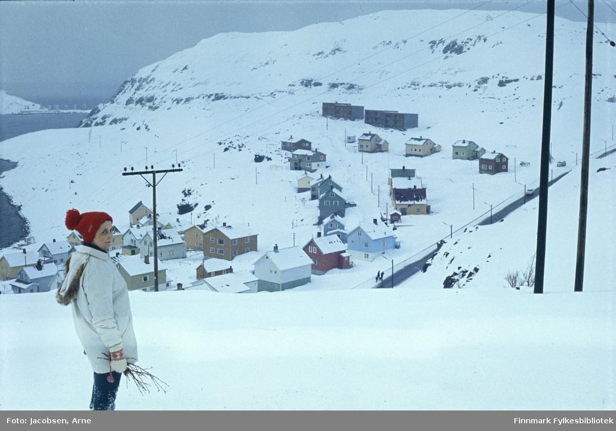 Aase Jacobsen på fjellet ovenfor Rypefjord en vinterdag med ganske mye snø på bakken. Hun har en lys anorakk med hette og skinnkrave, lue med dusk og strikkevanter på. I hånda holder hun noen kvister. Veien som går oppover til høyre er Rv94, Kubakken som er snøfri. Noen personer går langs veien og en bil er på tur oppover. Strømmaster til høyre på bildet og strømkablene går både nedover mot Rypefjord og mot Hammerfest. Husene midt på bildet er Svarthammeren og ned til venstre Mellomveien og Veita. Oppe til venstre er Rypefjell og ved enden av det er Rypklubbeidet med tankanlegget