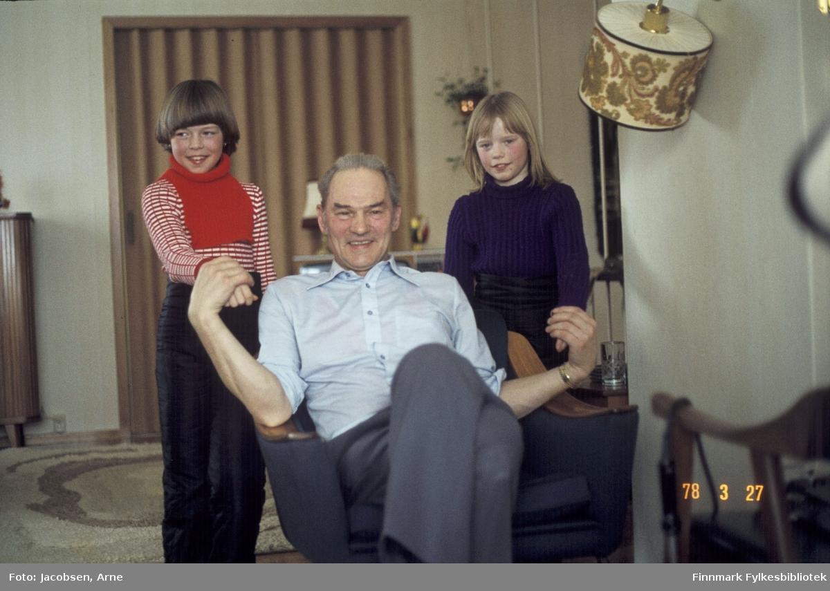 Alf Jacobsen med barnebarna Lene og Lise Antonsen. Han sitter i en lenestol og jentene står ved siden av. Alf har på seg en kortermet skjorte og bukse. Lise har mørk genser og Lene stripet, lys genser med strikket løshals over og mørke bukser. I bakgrunnen ses en foldedør og foran den, et skap med en bordlampe. Ved siden av Lise står en lampe og på gulvet ligger et ganske tykt teppe.