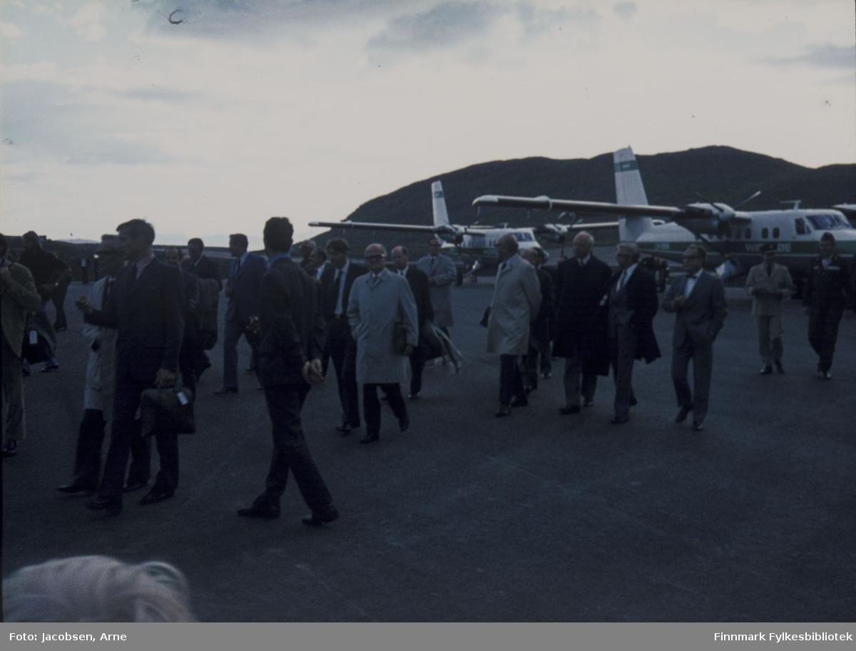 To Twin Otter-fly fra Widerøes flyveselskap parkert på Hammerfest lufthavn, med snuten mot Reindalen, under åpningen 30. juli 1974. Mange, pent kledde mennesker går rundt på flyplassen for å se og delta på åpningen. De går mot terminalbygningen og tårnet så visningen av flyene er nok over. Bak flyene ses fjellet Vardfjell.