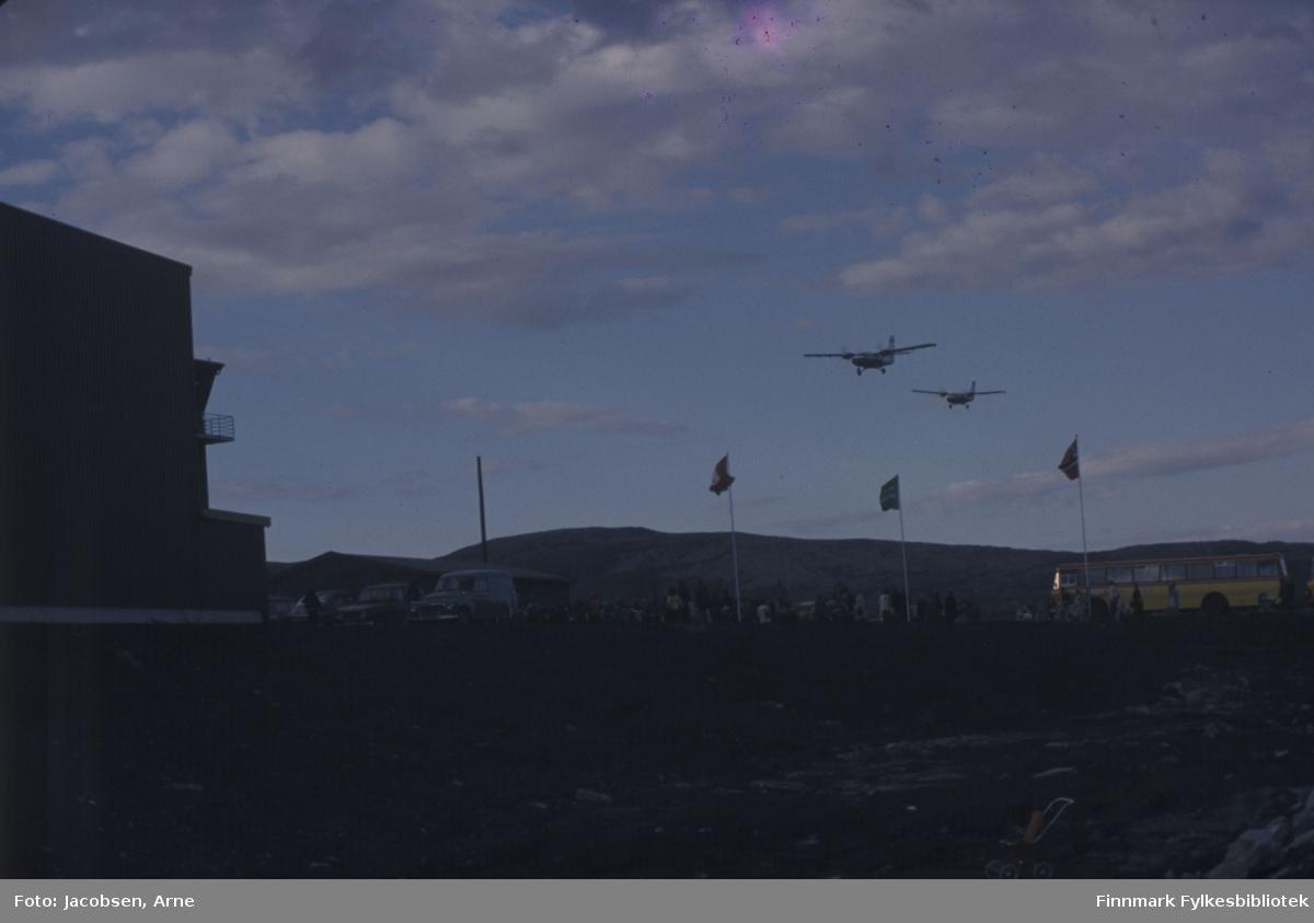 To Twin Otter-fly lander på Hammerfest lufthavn på åpningsdagen 30.07.74. Til venstre på bildet er hangaren og tårnet. Midt på bildet vaier Hammerfest- Widerøe- og det norske flagget. Til høyre står en FFR-buss som har fraktet noen av de mange menneskene som har møtt fram til markeringen. Terminalbygget ses bak de parkerte bilene. Delvis skyet og blå himmel over Reindalen som ses i bakgrunnen