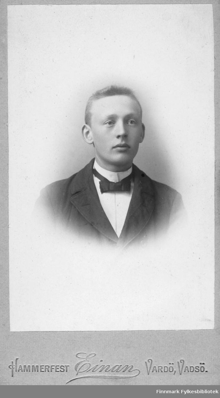 Portrett av ukjent ung mann. Han er kledt i mørk jakke og hvit skjorte. I halsen har han en mørk tversoversløyfe