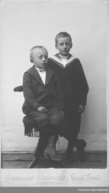 Portrett av to gutter. Gutten til venstre er August Magnus Jacobsen. Sønn av smedmester i Vardø Ole Sigfrid og hustru Anna Christine Vibe Jacobsen. Guttene er kledt i mørke jakker med slag, og mørke knebukser. Begge har sko som går opp på leggen og har knytting