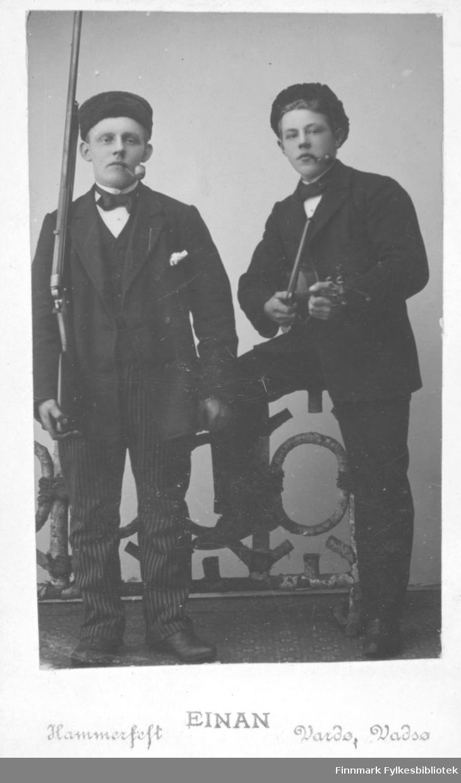 Portrett av to menn. Mannen til høyre er Johan Helmer Jacobsen. Sønn av smedmester i Vardø Ole Sigrid og hustru Anna Christine Vibe Jacobsen. Den andre mannen er ukjent. Johan Helmer er kledt i mørk jakke og stripete bukser. Hvit skjorte og mørk tversoversløyfe. På hodet har han en hatt uten brem. I munnen har han en pipe, og i hånden holder han et gevær. Den ukjente mannen er kledt i mørk jakke og bukser. Han har også hvit skjorte og en mørk tversoversløyfe. På hodet har han en hatt uten brem. Han holder en fiolin i hendene