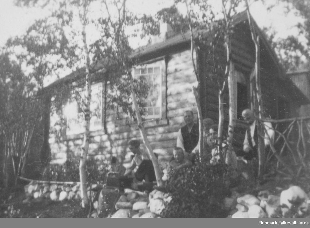 Bilde fra fotograf Olaf Adolf Jacobsen sin hytte ved Storskog som ligger ca. 13 km. fra Kirkenes i Sør-Varanger kommune. Det er seks personer på bildet. Mannen til høyre er Olaf Adolf. Hytten er en trebygning. Vinduene har sprosser. Rundt hytten er det bjørketrær og stein