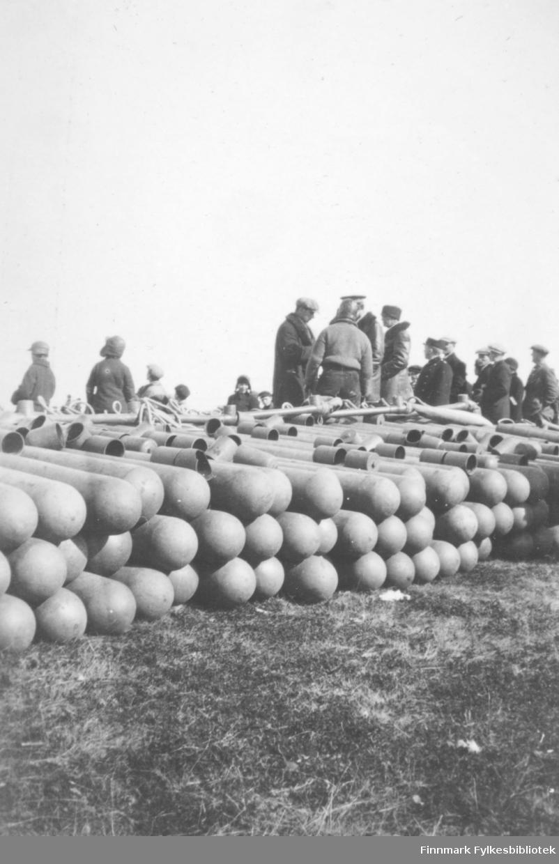 Fotografi av flere mennesker som står ved siden av  gassbeholdere som ligger på bakken. Bildet er sannsynligvis tatt i forbindelse med at luftskipet Norge var i Vadsø i mai 1926