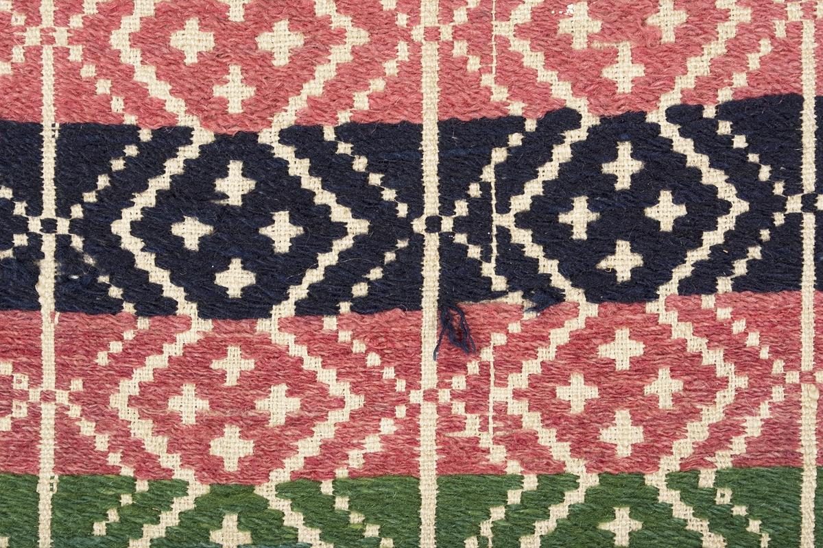 """Randigt täcke vävt i opphämta. Täcket är randigt på bredden i inslagsfärgerna rosa och mörkblått, varje rand är 43 mm bred. Ränderna på längden löper som sicksack-bårder med fyra kors i grupp inom varje rombformation. Runt om löper en grön bård i samma mönster som täcket i övrigt. Mönsterinslag i ullgarn på tuskaftsbotten i oblekt lingarn. Smal fåll i kortsidorna, stadkanter i långsidorna. Täcket är ihopsytt på mitten av två delar.Varp i oblekt 1-trådigt z-spunnet lingarn, 13,5 trådar/cm.Botteninslag i oblekt 1-trådigt z-spunnet lingarn, 10,5 trådar/cm.Mönsterinslag i 2-trådigt z-tvinnat ullgarn.Märkt på baksidan med en påsydd tyglapp med texten: """"N° 154 a Rönnebergs"""".Täcket har också varit märkt med en fastnästad brun pappersetikett (nu förvarad i reg.pärm) från Svenska Hemslöjdsföreningarnas Riksförbund, med tryckt och maskinskriven text: """"Föreningens namn: Malmöhus läns Hemslöjdsförening Malmö. Föremålets art: Gammal täcke Rönneb. h:d. Föremålets storlek: 120 + 165 Teknik: opphämta Teknikens ortsbenämning: Skälblad Material: Linne & ullgarn. Försäljningspris: -  Kopia, bearbetning eller komposition: - Utfört av:  - """"."""