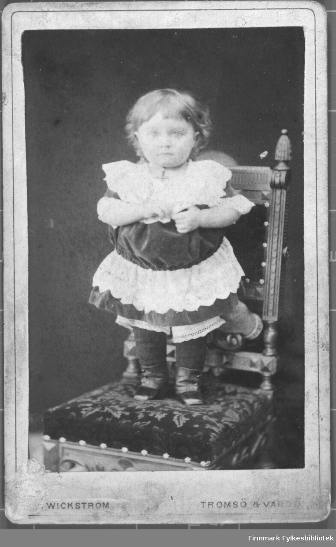 Portrett av barn jente i kjole hun står på en stol. ateliere studio fjeset hennes er uskarpt Albumet med bildet kommer fra Ekkerøy, kanskje han kommer derfra.