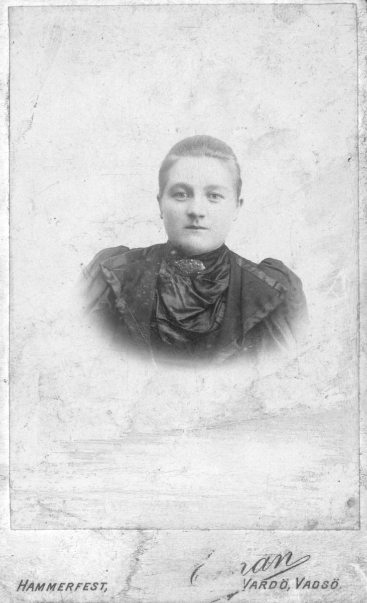 Portrett av ukjent kvinne. Hun er kledd i kjole og har en brosje rundt halsen. Bildet rolig tatt på slutten av 1800-tallet, begynnelsen av 1900-tallet.