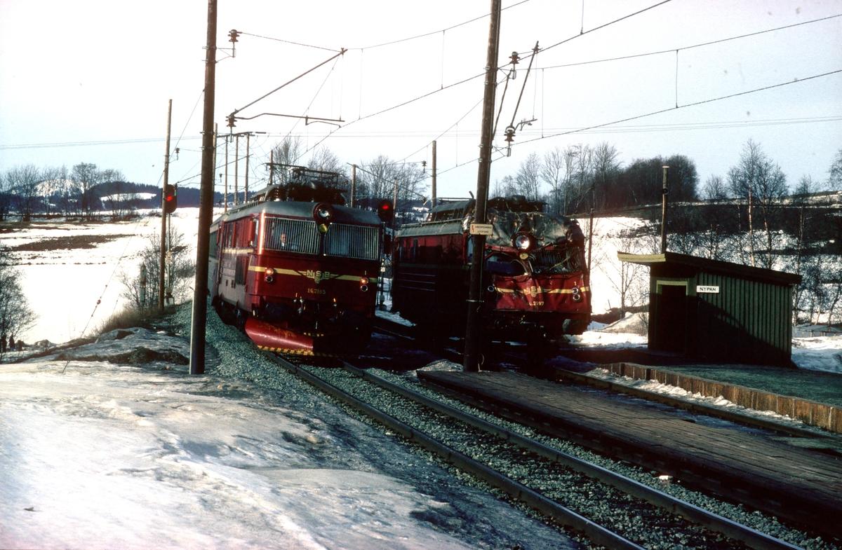 Ekspresstoget Dovreekspressen, tog 42, kjører forbi El 14 2197 på Nypan stasjon. 2197 er satt på traller etter kollisjon og skal fraktes til Grorud.