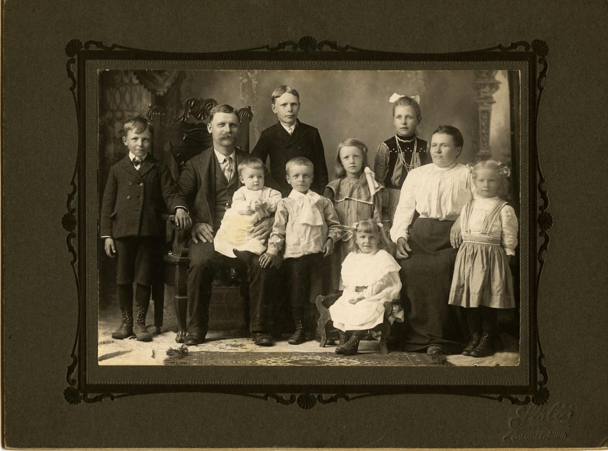 Familieportrett av familien Petter og Ida Johanne Pelto med åtte barn. Familien kommer opprinnelig fra Vadsø men emigrerte til USA. Bildet er antagelig tatt i Calumet, Michigan. Alle er kledd i finstas.