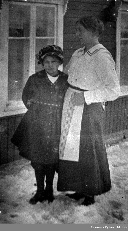 Barn og kvinne foran familien Gunnaris hus. Kvinnen er trolig tjenestepike for familien. 1920 tallet.