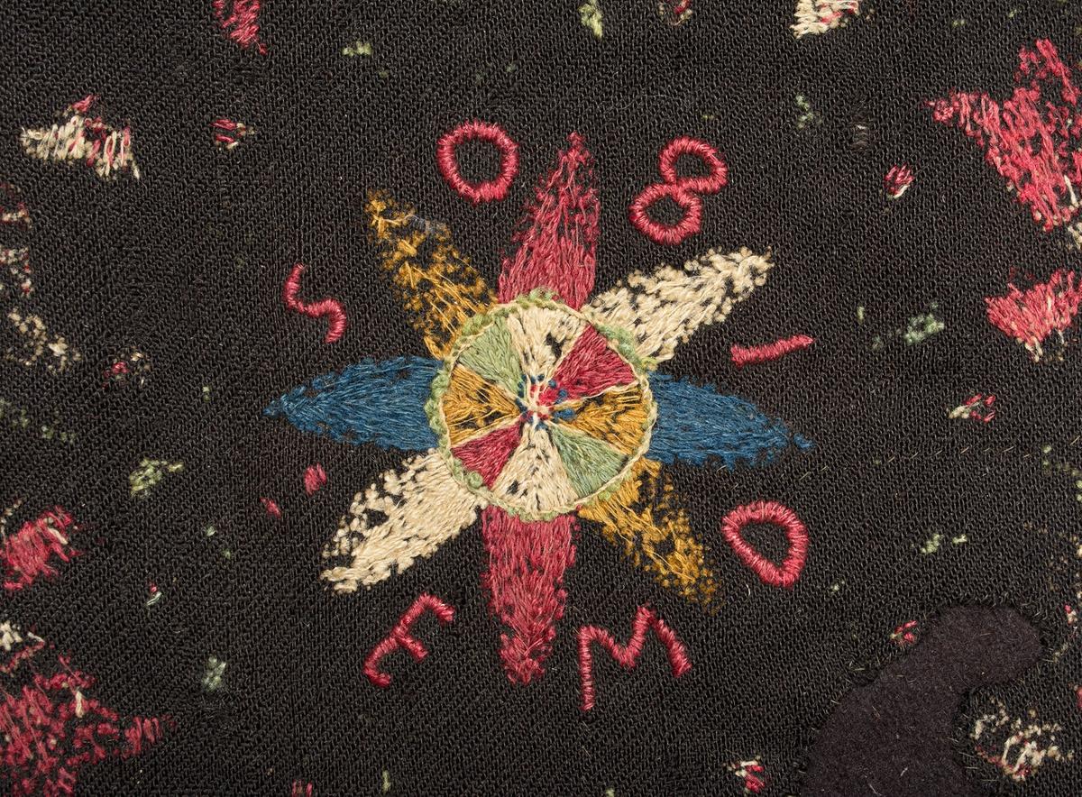 """Kudde i yllebroderi. Broderi med kulört 1- och 2-trådigt ullgarn på svart/brunt ylletyg i 3-skaftad kypert. Stjärna på mitten med blomkrans runt om. Sydd märkning, runt stjärnan, i plattsöm med rött garn: """"E M D 1805"""". En blomma på själk i varje hörn. Sydd med rött, gult, grönt, blått och naturvitt ullgarn. Baksida saknas, rester efter fyllning - av fjäder. Lappad på baksidan med tätt ylletyg.Helmontering/förstärkning på bomullsväv."""