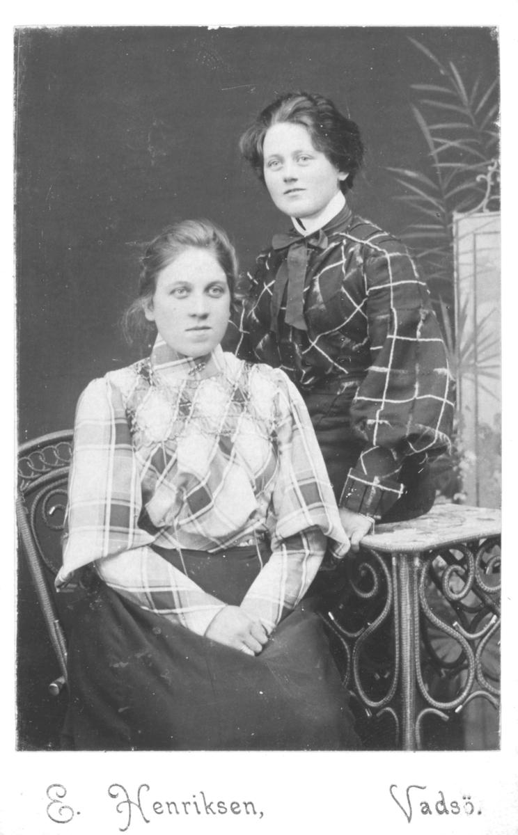 """Portrett fra to unge kvinner, Alfine (Rolfstad) og Olga Marie Pedersen. Alfine blir identifisert som """"Rolfstad"""" på bilde FBib.96010- 005, men egentlig het hun trolig Vollstad til etternavn. Alfine sitter på en stol og Olga lener seg på et lite bord. Begge er kledd i rutete bluser med lange, mørke skjørt.   Alfine Vollstad var født 25.11.1883 i Vadsø. Hun var gift med Andreas Vollstad (født 22.08.1881 i Dverberg), han var lærer, kirkesanger og herredskasserer i Loppa kommune med bosted Øxfjord under folketellingen i 1910.   Olga Marie Pedersen var født 11.09.1886 i Vadsø og døde i Kiberg i 1912, 27 år gammel. Hun var registrert som kontordame og ugift, i Ministerialbok for Vadsø Prestegjeld i 1912. Oga Marie bodde i Toldbodgaden, i bakbygningen, i Vadsø i 1900. Hun var datter av Nanna Evida Pedersen (født Jonas i Thomaselv, Vadsø i 1862) og Vexel Pedersen som var portner ved Politistasjonen og kommunalt bud. Nanna Evida var sydame og hennes far kom fra Alkula, Finland og moren fra Torneå, Finland. Jentene er fotografert hos fotograf Emilie Henriksen, Vadsø."""