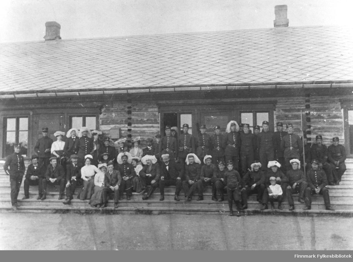 35 mann i militæruniform, 7 kvinner og fire gutter har stilt seg på trappa i militærbase i Nyborgmoen. En del av soldatene og kvinnene har myggnetter på hattene, en del av barna er kledd i knebukser.