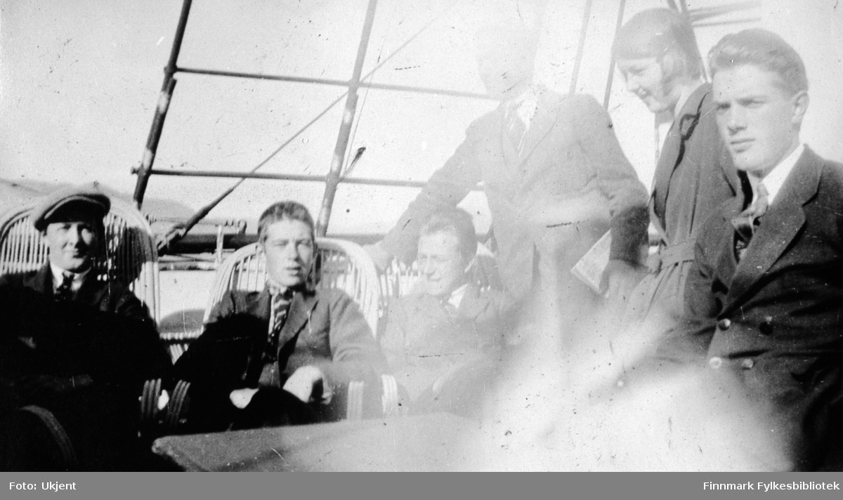 Her poserer en gruppe med folk ombord et skip som trolig er Hurtigruten. Alle er ukjente. De fleste av dem sitter på stråstoler. Gutten helt til venstre har på seg en lue. Guttene har på seg slips, jakke og bukser. På jakken til gutten som sitter helt til høyre kan man se syndlige knapper. En jente står mellom to av guttene til høyre. Hun har på seg en kåpe. I bakgrunnen kan man se fjell.