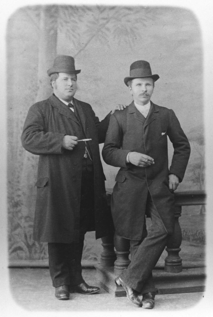 Portrett av kjøpmannen Bastian Moe og herr Kjellmann (fornavn ukjent) tatt i studio med malt bakgrunn. Begge menn poserer med sigar foran en tidstypisk malt bakgrunn for å illudere landskap. Herrene bærer hatt og frakk og mannen til venstre har et urkjede i vesten.