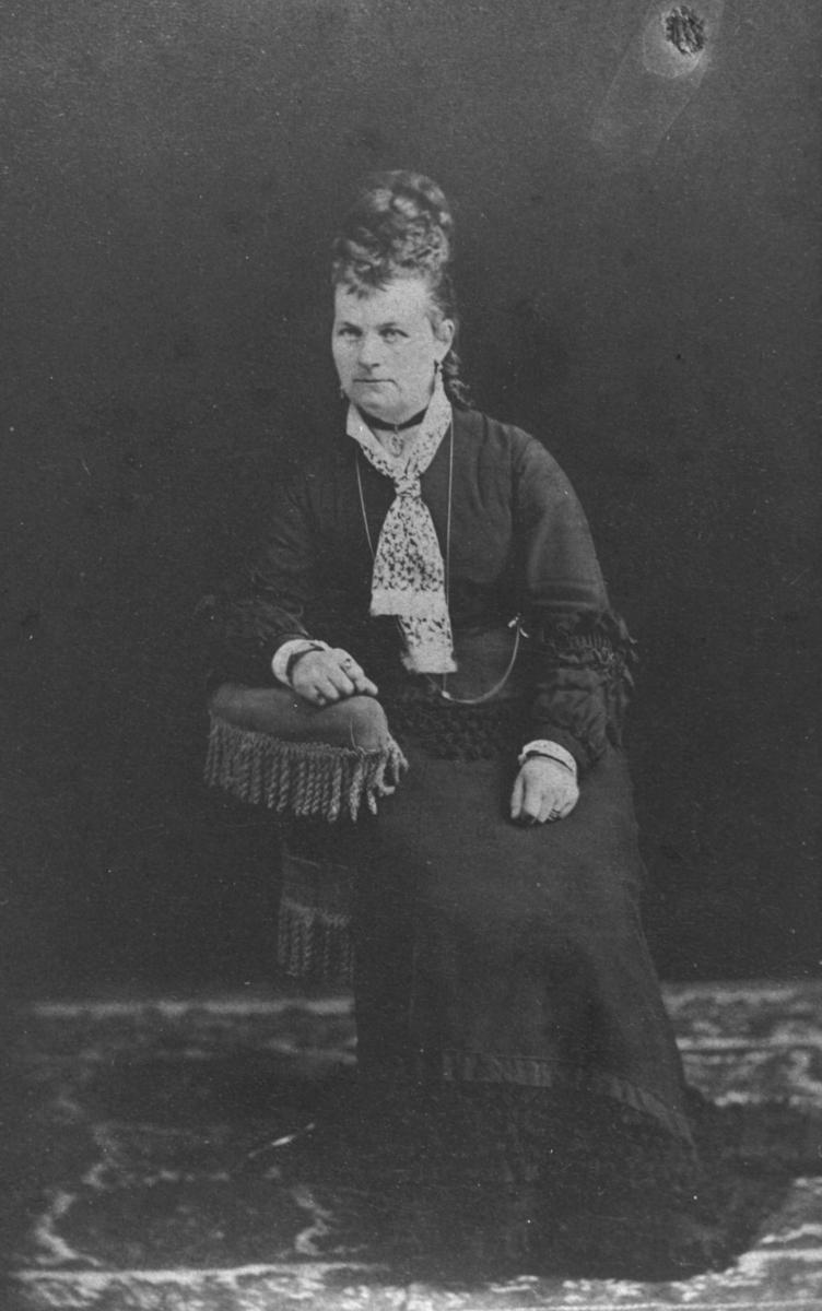 Visittkortportrett av en russisk kvinne med 'høy' frisyre. Kvinnen sitter på en lenestol med armen på ryggstøet. Stolen, bakgrunnen og gulvet er samme som på bilde fb.96009-020