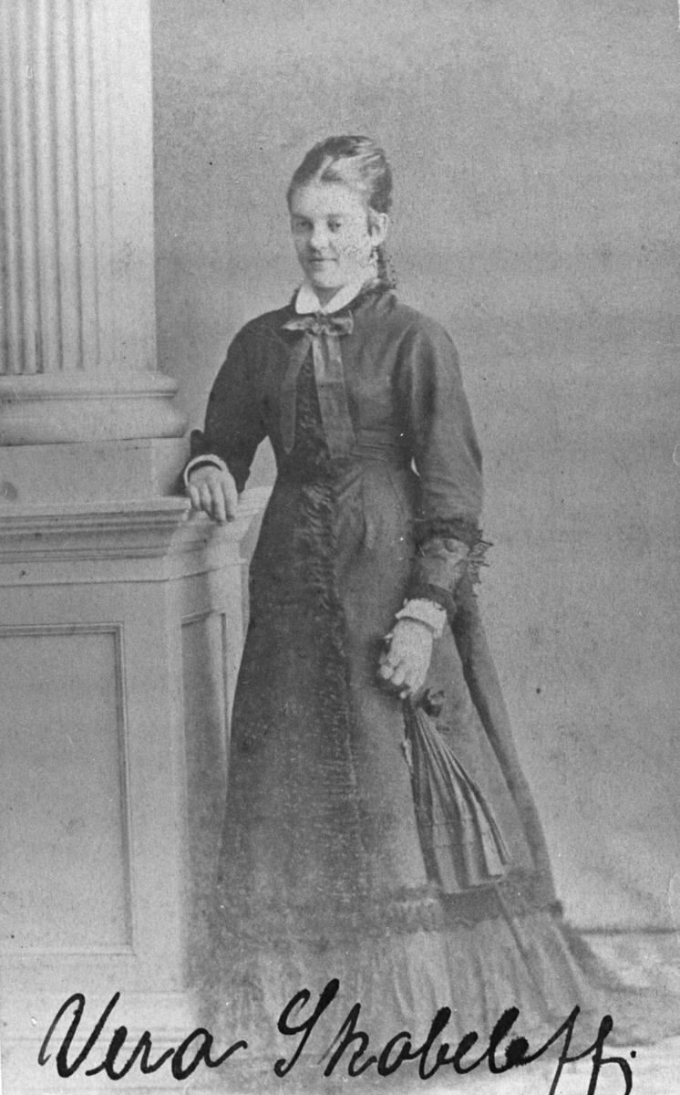 Portrett av en ung kvinne, Vera Skobleff, fra Arkhangel Russland. Bildet er gammelt, tatt ca 1860, kanskje tidligere. Kvinnen står ved en stolpe og er kledd i en lang mørk kjole med hvit krage og en stor sløyfe. På handen har hun en liten dameveske eller sammenslått vifte i stil med kjolen. Dette bildet er nesten identisk med fb.96010-009