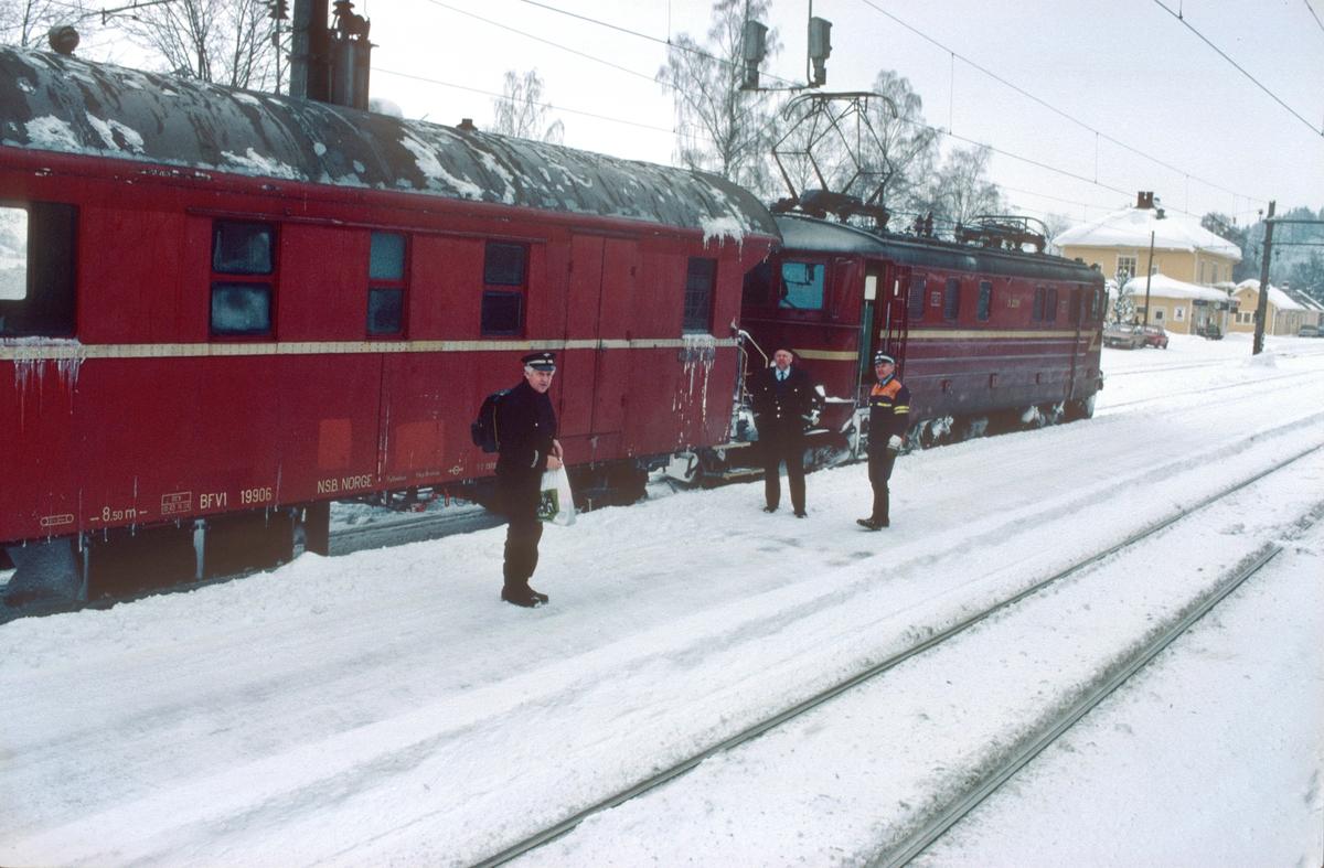 """Personalbytte i godstog på Roa stasjon. Godstog 5174 har ankommet fra Eina og lokomotivføreren skal bytte med føreren i godstog 5165 (Alnabru - Roa). Førertjenesten i godstogene mellom Alnabru/Grefsen og Roa, og mellom Hønefoss og Eina, ble dekket av lok.personale stasjonert Hønefoss (NSB Oslo Distrikt). Togførertjenesten ble kjørt av konduktører som også var stasjonert der. Lokomotivførerassistenten i 5165/66 var stasjonert Oslo. På bildet ser vi lokomotivførerne og overkonduktøren (""""Togføreren"""" - med arbeidstøy). Overkonduktørene på Hønefoss som var stasjonert Oslo distrikt hadde mest godstogtjeneste."""