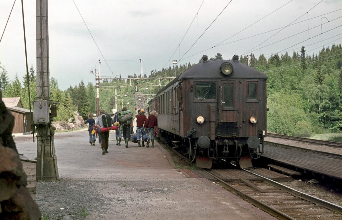 Lokaltog til Oslo Ø har stoppet på Movatn stasjon i Nordmarka. Turgåere med ryggsekker går om bord.
