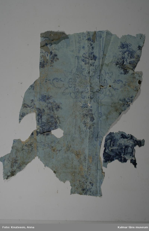 KLM 39790:2. Tapet. Tittskåpstapet. 2 st bitar. Blå tapet i olika nyanser. Ett slags stort medaljongmönster med titthålsbilder på en ryttare som låter sina två hästar dricka. Tapeten har i ursprungsskicket haft en mycket blåare färg. Det syns tydligt på den mindre biten som förmodligen har suttit skyddad. Datering: 1860-tal.