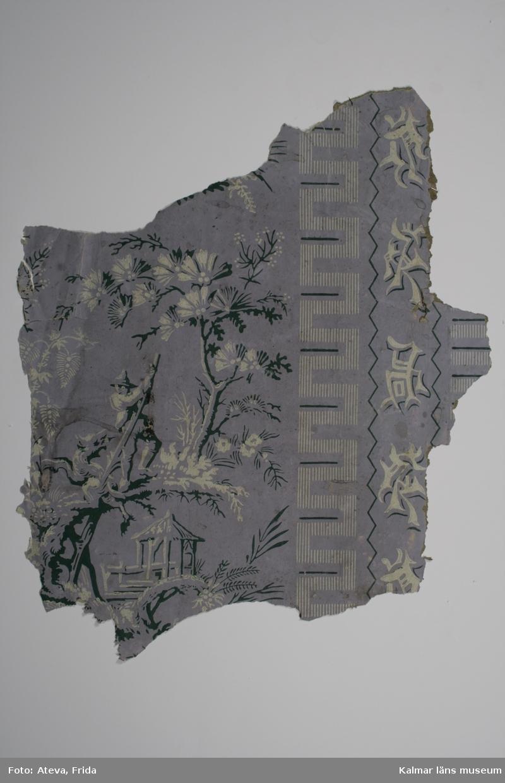 KLM 43797. Tapet. Tittskåpstapet. Av papper. Lila tryckt botten och mönster med lodräta vita och gröna asiatiska tecken samt bild med hydda och träd (Ginko biloba?). Man med toppig hatt som motar bort ett odjur med hjälp av en lång pinne. Datering: 1850-1870-tal.