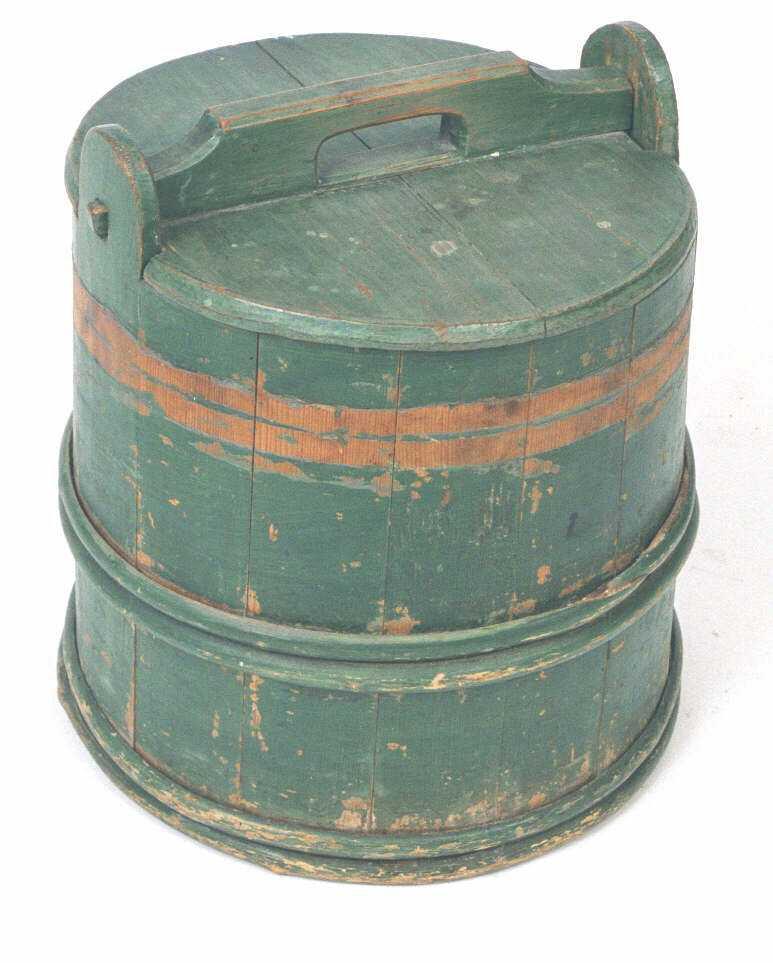 Tine, med lokk. Furu. Grønn malt.  Sylinderformet, med skrå vegger. Sidene i form av buede bord, felt  inn i bunnen.   Lagget  i tre avdelinger.  Lokk i et stykke, bærelist kilt ned,  med hull til håndtak.