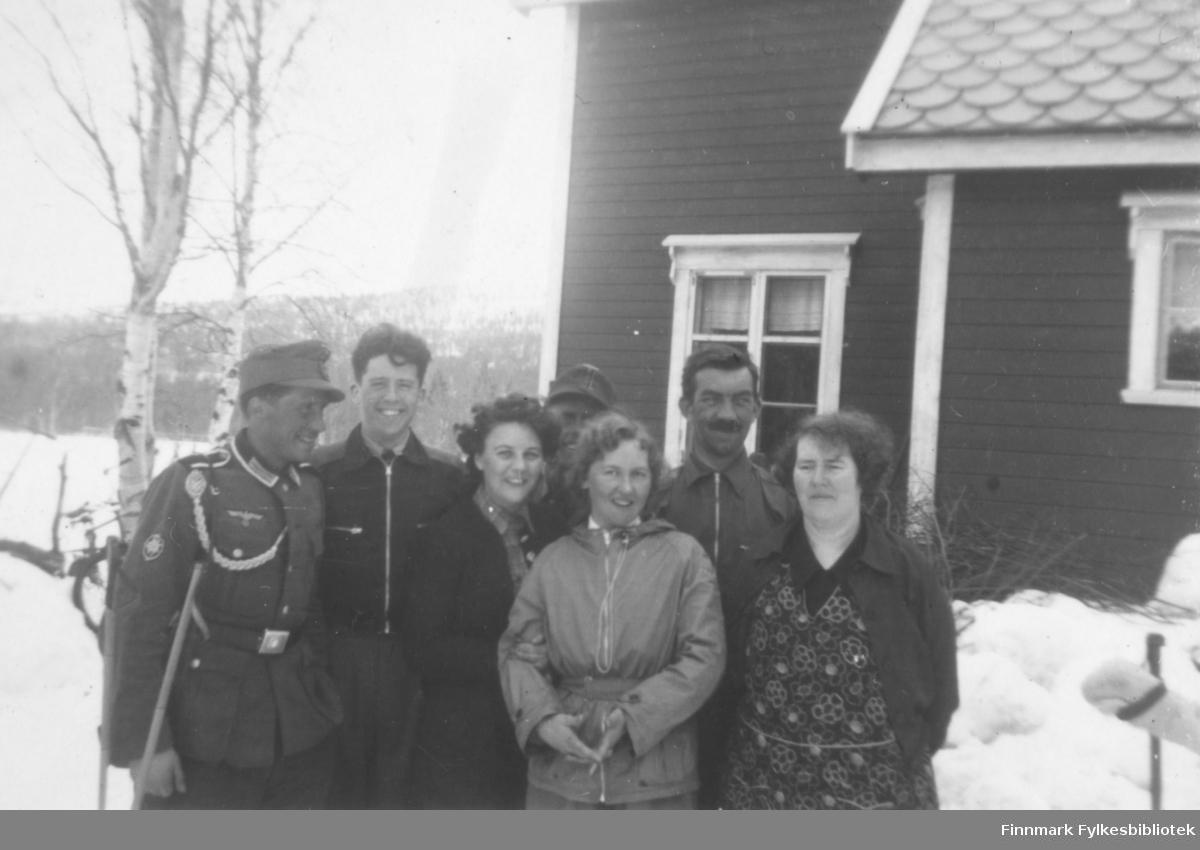 Altafolk i Gargiadalen under 2. verdenskrig. Fire menn og tre kvinner. To av mennene er uniformskledd. På sidene ser vi noen skistaver stukket ned i snøen og i bakgrunnen trær og et bolighus. Ca.1935-1945.