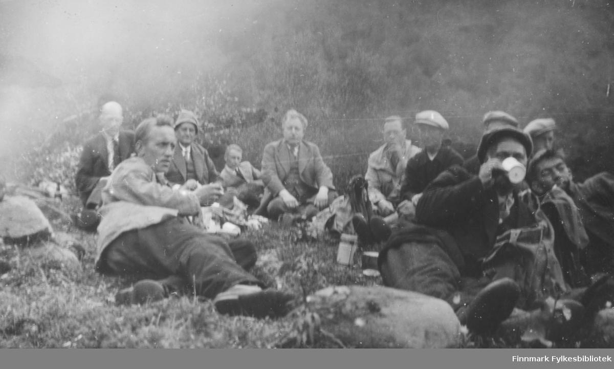 Elvebåtstakere sitter samlet i bakken, trolig for en matpause. Flere menn i dress og slips er med. Antagelig 1930 tallet.