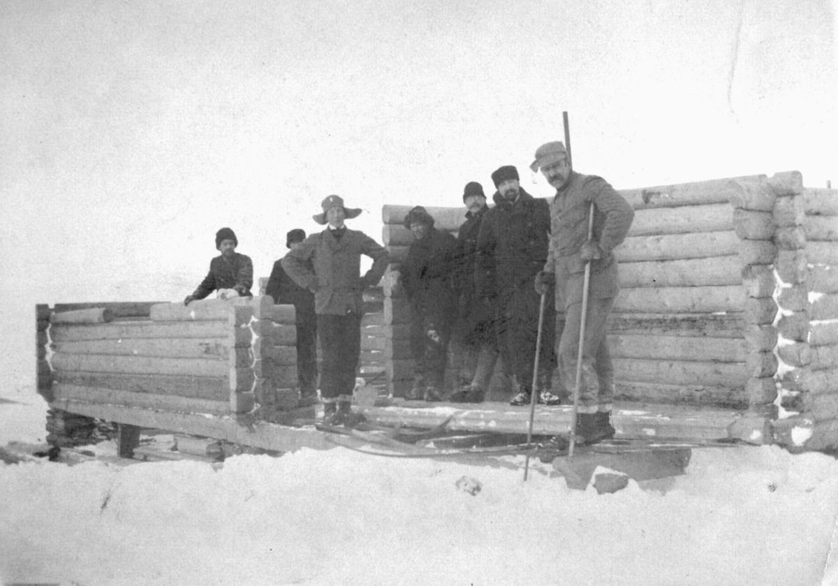Bildet er trolig tatt på begynnelsen av 1900-tallet. Flere menn poserer foran en uferdig hytte. Mannen helt til høyre har på seg ski og holder staver i hendene. Det antas å være Eilert Nikolai Brodtkorb. Hytten kan være den uferdige skihytta ved basis A i Vadsø. Enkelte av mennene på bildet har bart og skjegg. Mennene er kledd i jakker, bukser, sko og luer. Bygget blir laget av tremateriale. Bakken er dekket til med snø.
