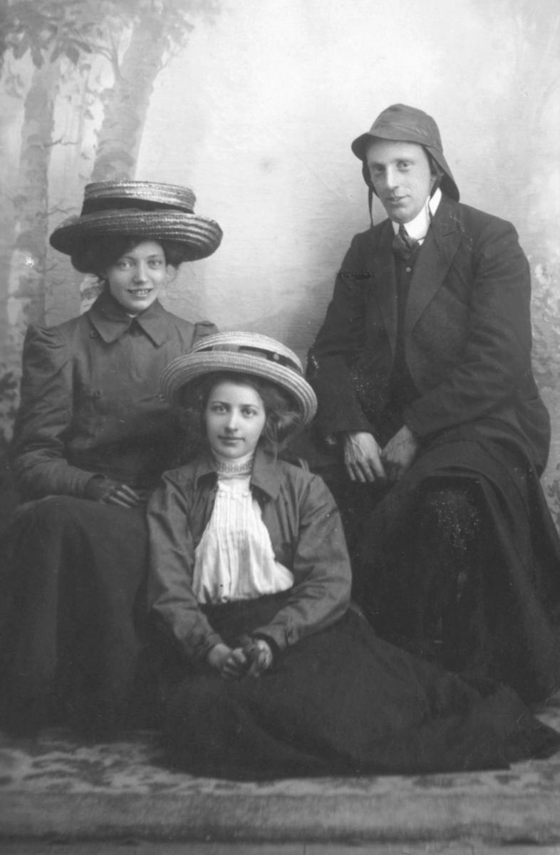 Et gruppeportrett. Inga Brodtkorb (gift Hollum) er kvinnen som sitter på krakk til venstre. De to andre er ukjente. Begge pikene har på seg store stråhatter, skjørt, jakke og hansker. Piken som sitter på gulvet har også på seg en syndlig skjorte. Rundt halsen har hun noe som kan ligne et smykke. Mannen til høyre har på seg sydvest og slips. Gruppen sitter foran en malt bakgrunn.