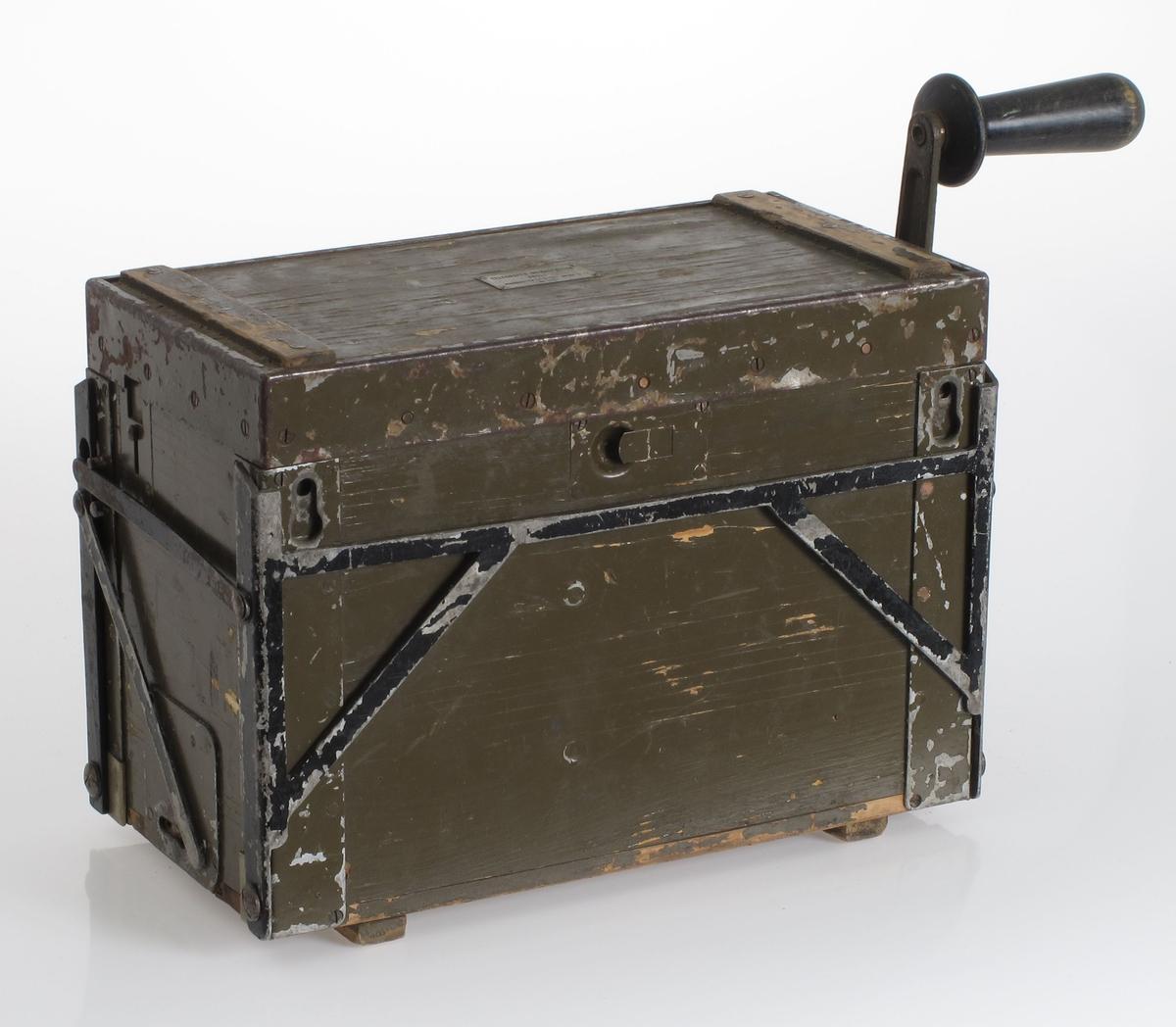 Lampe med dynamo som sveives. Ligger i transportkasse forsterket med jernbeslag. Malt jordgrønn. Kassa inneholder også reservedeler, som lyspærer.   Virkemåten er som en gammeldags sykkellykt. En lampe med glødetrådlampe lyser når dynamoen dreies rundt. I dette tilfelle dreies dynamoen med en sveiv  (med svinghjul).   Papir med innholdsfortegnelse på lokkets underside.