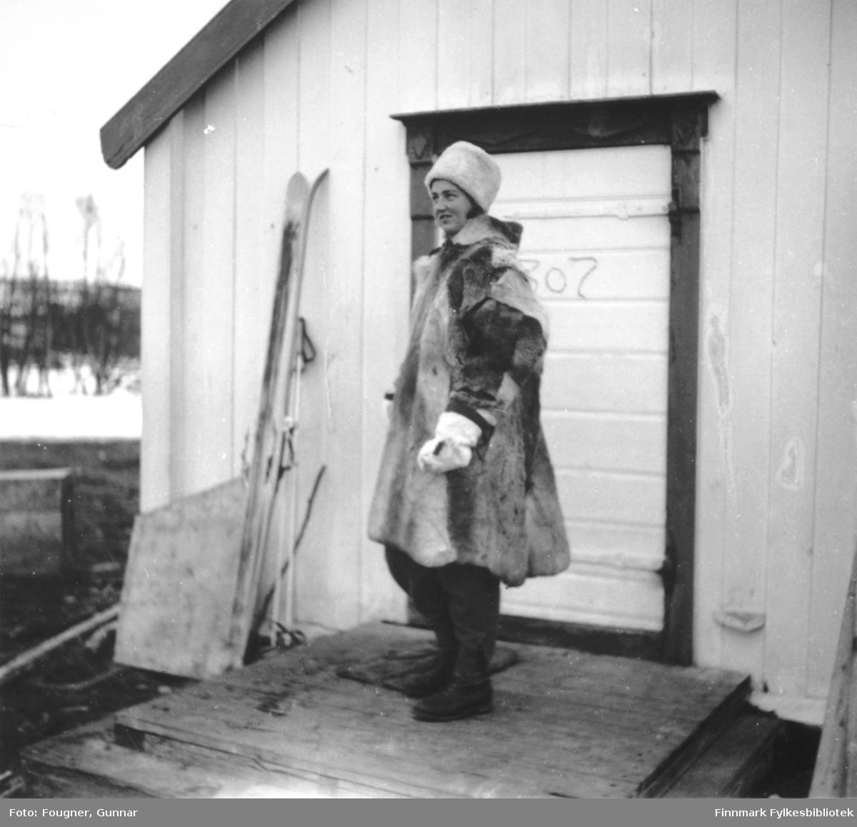 Sykepleier utenfor Karasjok kirke. Hun kom ned i fallskjerm med troppene som kom i januar 1945. Hun er kledt i pesk og skinn- lue. Et par ski står lent mot kirkeveggen.