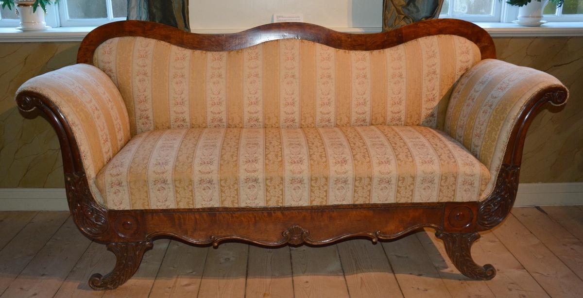 Rektangulær sofa med treramme rundt hele formen.Beina er skrådd utover med dekor av blad i treskjæring. Utskjæringer også foran og på armlenene. Treverket på ryggen er helt glatt. Trerammen er lakkert. Sofaen er stoppet,tøyet er delt inn i langsgående blomsterornamentikk.