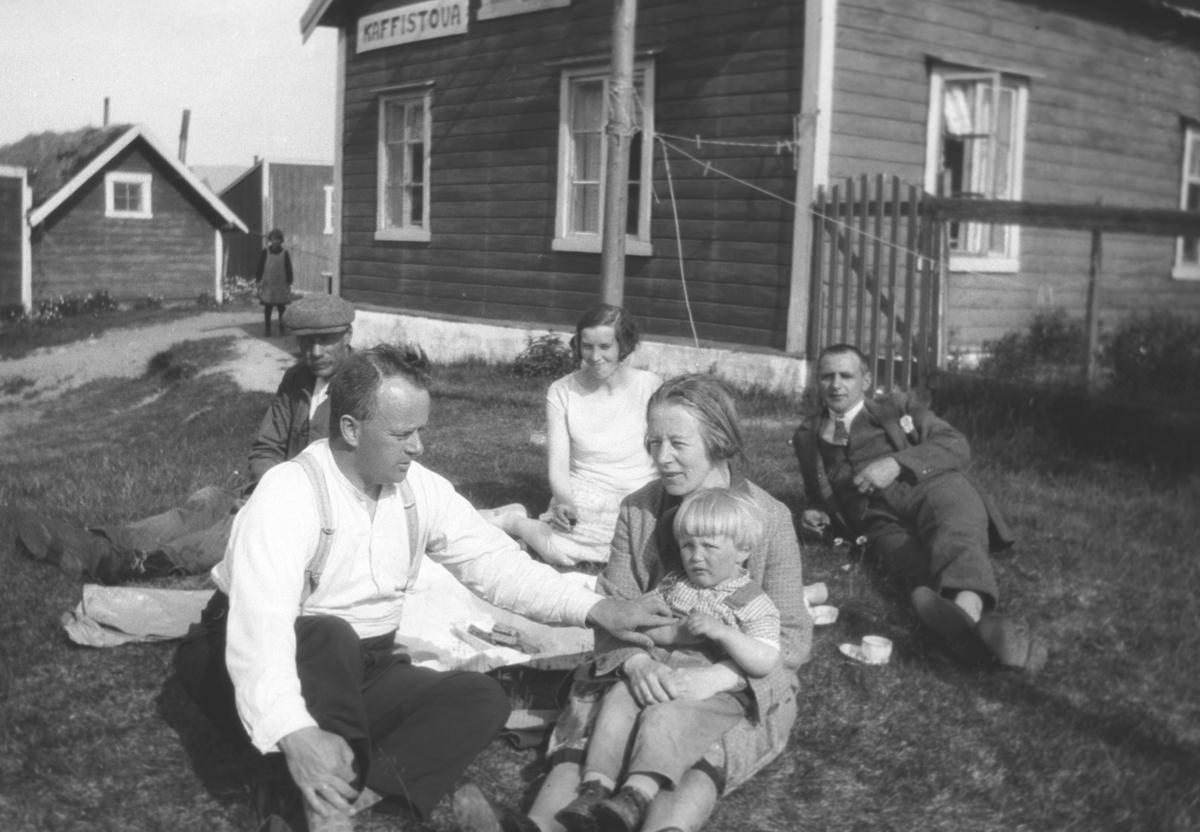 Flere personer sitter på gårdsplassen utenfor Kaffistova. Bakerst i bildet sitter Frida Hauge i lys kjole. Stedet er ukjent.