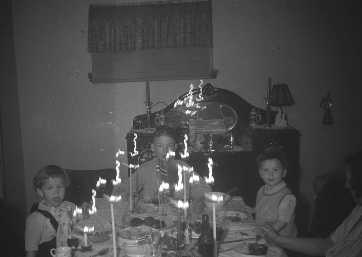Julefeiring hos familien Hauge under krigen. Barna på bildet er fra venstre: Øystein Hauge, Tor Hauge og Rolf Hauge. Helt til høyre på bildet ses såvidt en dame. Dette kan være Frida Hauge.