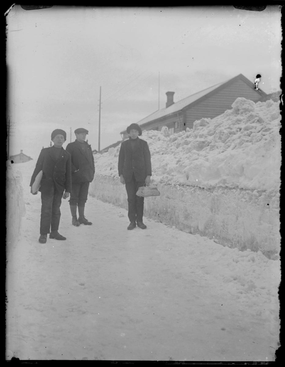 Tre unge menn står på en vei, to av dem bærer pakker. Det er høye brøytekanter. To er kledt i langbukser og skinnluer mens den tredje har knebukser og caps
