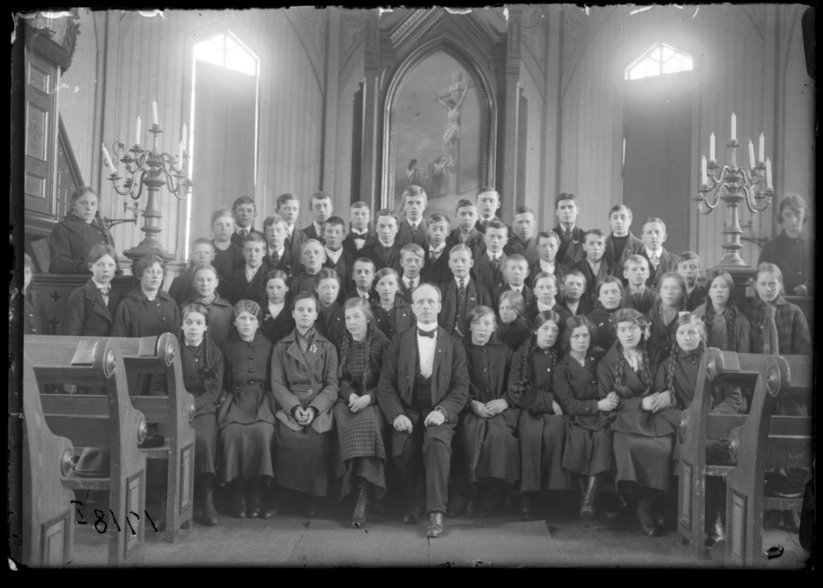 Konfirmanter, Vardø 1918. Bildet er tatt inne i kirka. Midt i første rekke presten Johan Oskar Grasmo