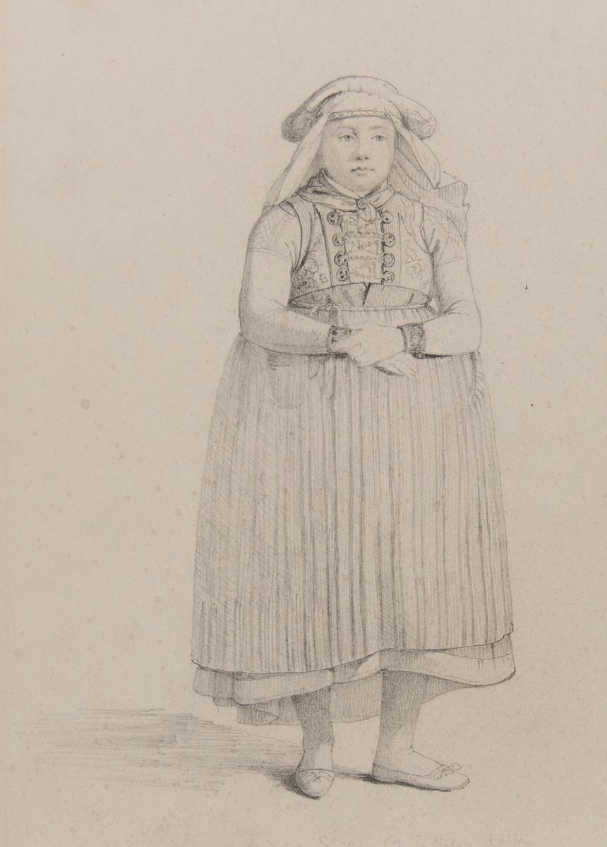 Sisela Christensdotter, Knestorp, Bara Härad. Blyertsteckning av Otto Wallgren. Studie framifrån av kvinna i dräkt , stående i helfigur med beskrivande text