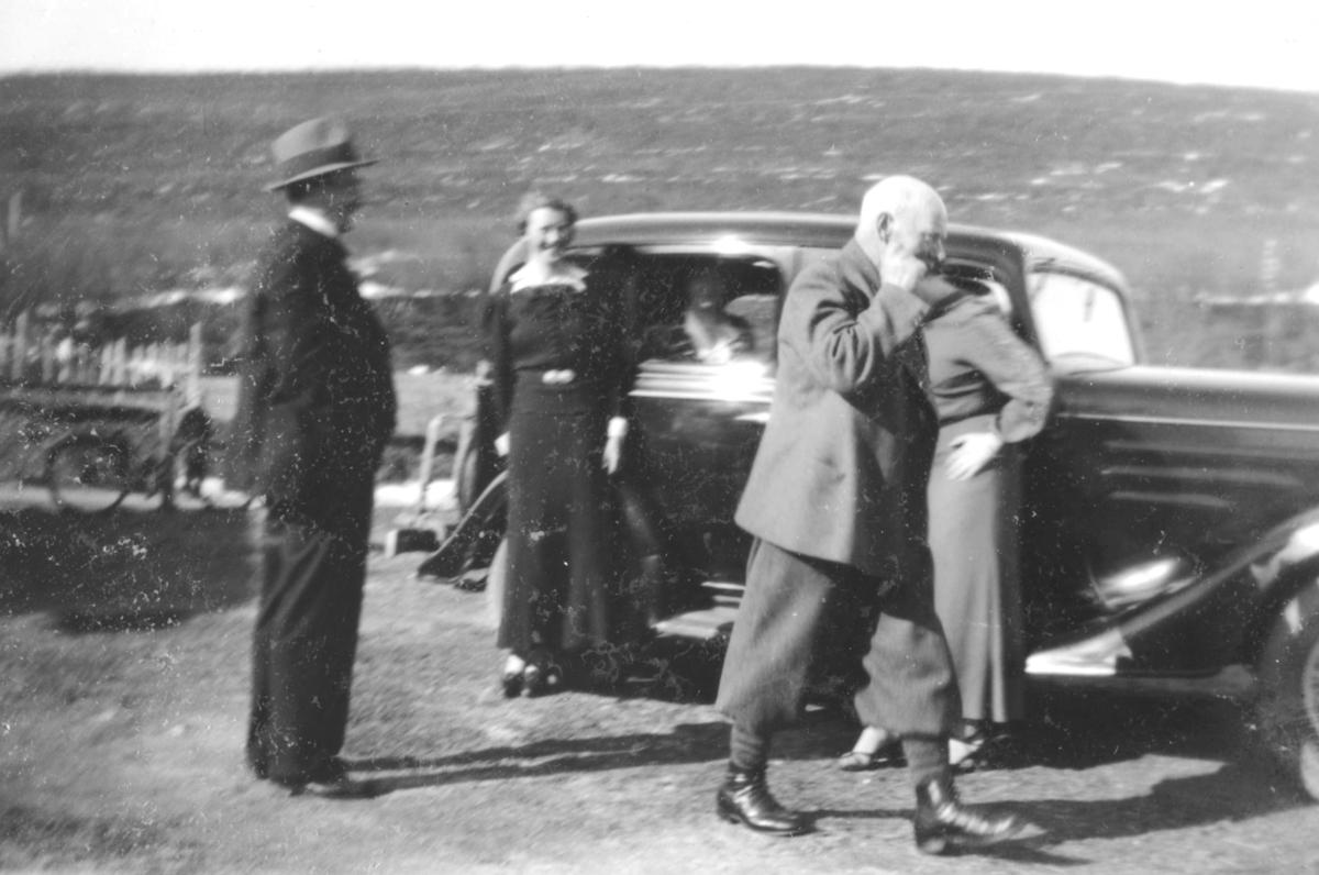 Damer og menn som står ved siden av en bil, en Chevrolet 1934 modell.